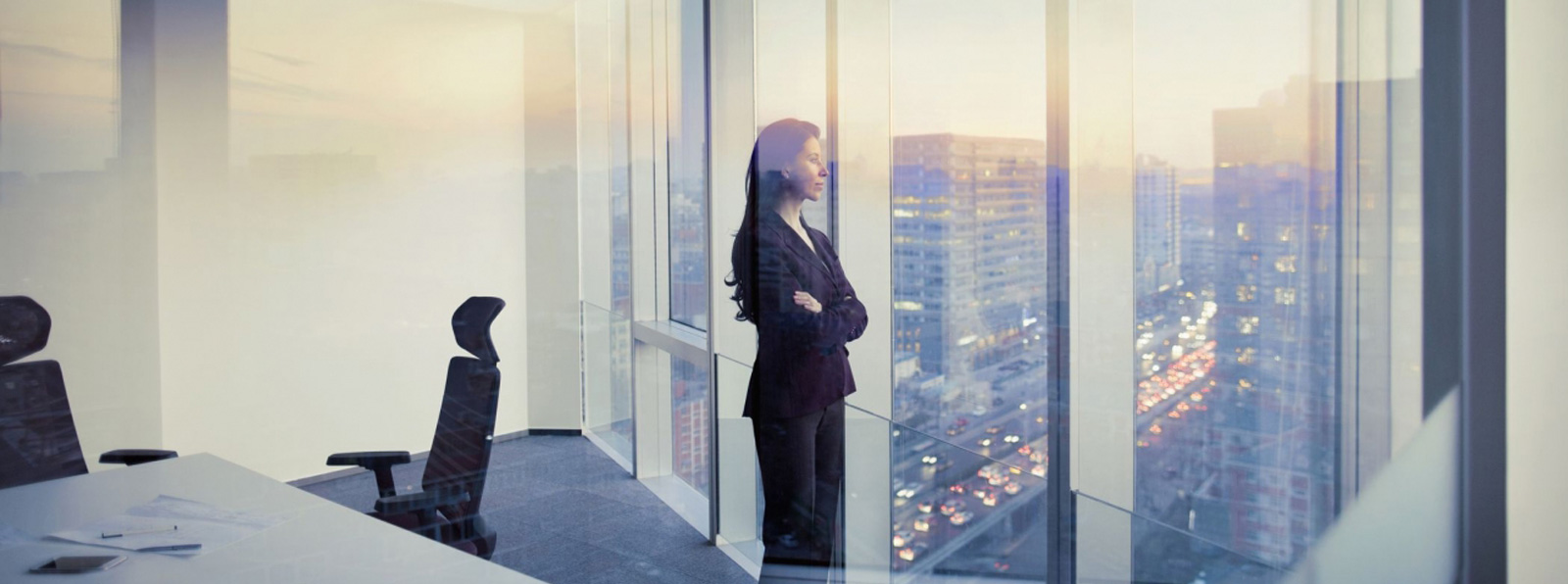 a woman in an office staring at the city on the outside of a building with glass walls