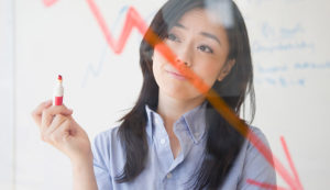 a corporate woman holding an orange pen and drawing graphs on a glass board