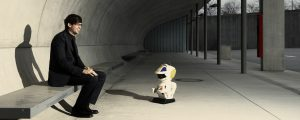 man in black suit sitting together with a white robot