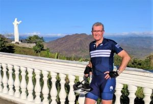 PBO Global director in his blue lycra with a religious statue and mountains at the background