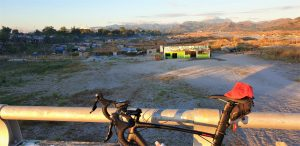 red road bike parked on a bridge with a view of Luzon valleys and a small rural community