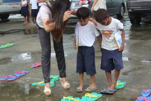 a female teacher guiding two young boy students into fitting new green slippers