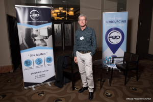Director of PBO Global standing beside its booth at the CAFBA Annual Conference 2019